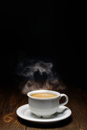 Hot coffee with steam in white ceramic cup on dark wooden backgound. Heart shaped steam