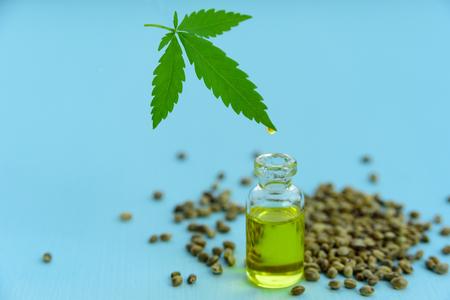 Hemp oil in glass bottle, seeds and leaf on light blue background. Leaf levitating over the jar