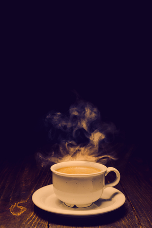 Hot coffee with steam in white ceramic cup on dark wooden backgound. Vintage toning, duotone Reklamní fotografie