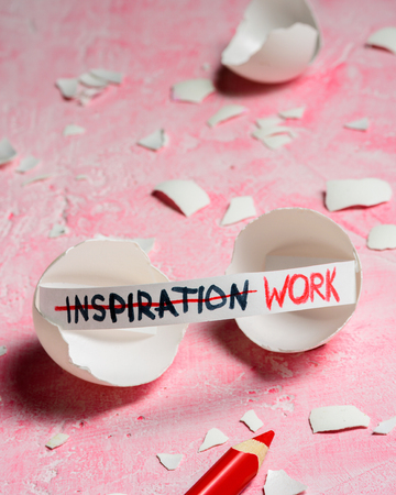 Work hard and inspiration concept. Cracked egg on pink background with text INSPIRATION and WORK. Like fortune cookies
