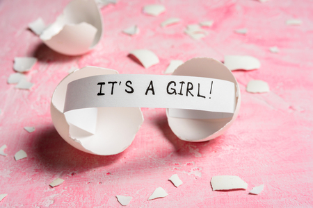 Baby shower concept. Girl, pink. Cracked egg with a message ITS A GIRL. Like fortune cookies Reklamní fotografie
