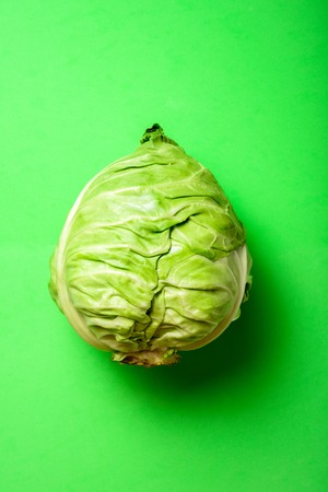 Fresh cabbage head on light green background