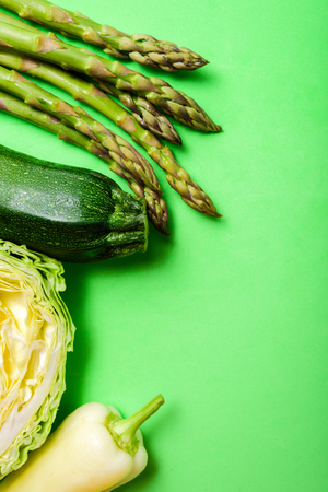 Green vegetables on green background. Asparagus, zucchini, cabbage and bell pepper