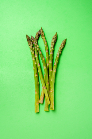 Bunch of fresh asparagus on green background