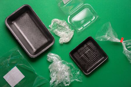 Plastic used disposable food package on green background. Plastic waste, recycle concept. Top view, flat lay