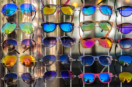 Range of colorful sun glasses on rack in street shop