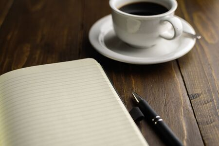 Black coffee, pen and notebook on dark wooden table. Working place