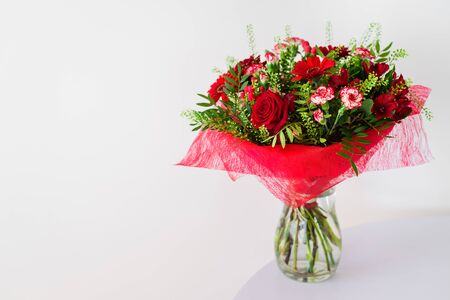 Beautiful red flower bouquet with roses in glass vase on grey background Stock Photo