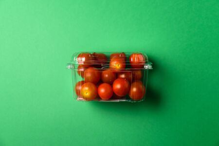 Fresh cherry tomatoes in plastic package. Zero waste, recycle concept. Plastic pollution. Green background Stock Photo