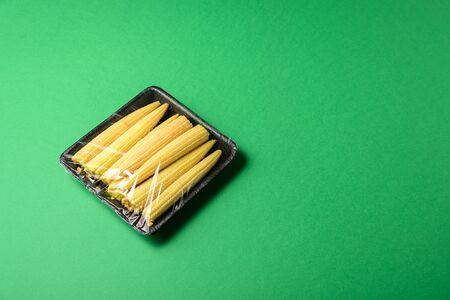Fresh baby corn in plastic package. Zero waste, recycle concept. Plastic pollution. Green background Stock Photo