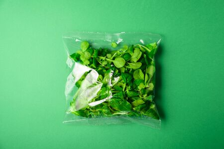 Fresh baby greens in plastic package. Zero waste, recycle concept. Plastic pollution. Green background