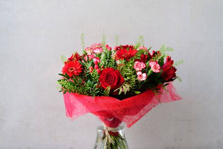 Beautiful red flower bouquet with roses in glass vase on grey concrete background Stock Photo