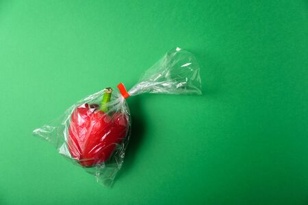 Fresh bell pepper in plastic package. Zero waste, recycle concept. Plastic pollution. Green background