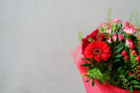 Beautiful red flower bouquet with roses on grey concrete background