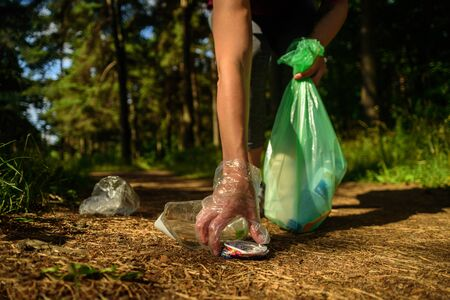 Woman collecting garbage in forest. At jogging or running. Plogging concept Banco de Imagens