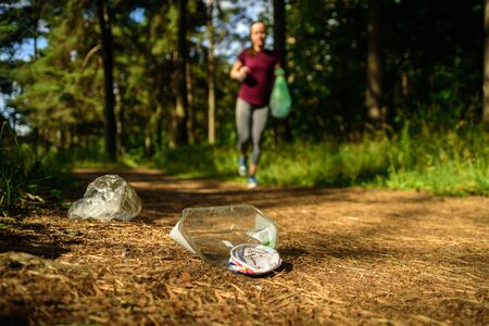 Woman jogging with garbage bag in forest. Collecting trash. Plogging concept Banco de Imagens