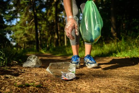 Woman collecting garbage in forest. At jogging or running. Plogging concept Stock Photo