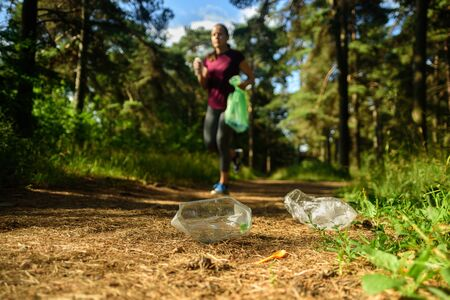 Woman jogging with garbage bag in forest. Collecting trash. Plogging concept Stock Photo