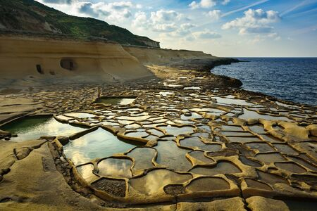 Salt evaporation pans on Malta. Ponds near sea filled with water at sunny day, february 2019