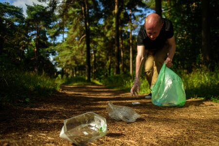 Man collecting garbage in forest. At jogging or running. Plogging concept Stock Photo