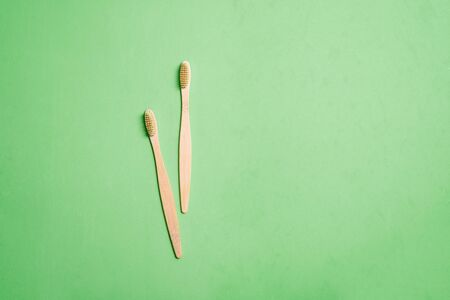 Two bamboo wooden toothbrushes on neo mint trendy background