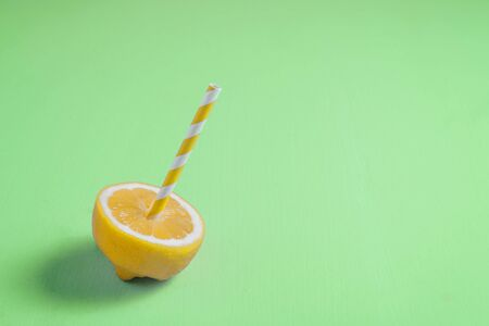 Lemon half with paper straw on neo mint trendy background. Summer, fresh and fun concept Banco de Imagens