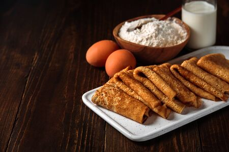 Russian pancakes blini with ingredients on dark wooden background