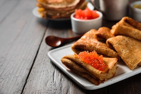 Russian pancakes blini with red caviar on wooden background