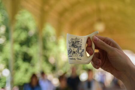 Man holding special mug for water from hot mineral spring in Karlovy Vary