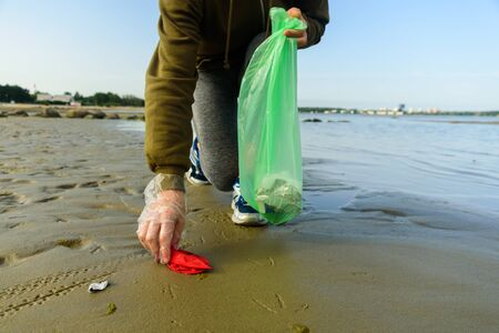 Woman picking garbage on beach. At jogging or running. Plogging concept