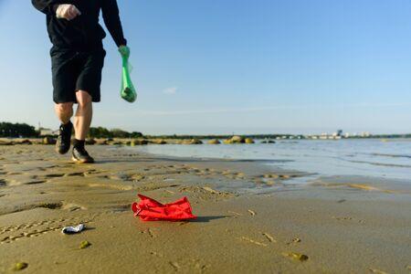 Man picking garbage on beach. At jogging or running. Plogging concept