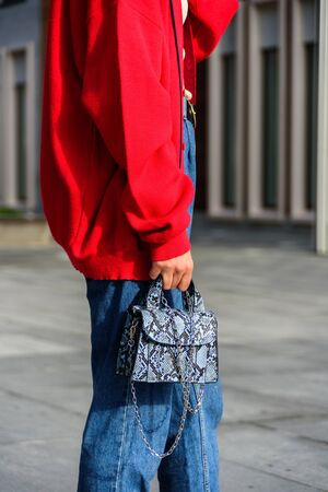 Close up of woman in red oversize cardigan. Blue denim jeans. Street style