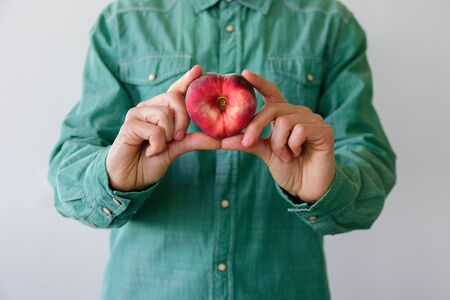 Man in green shirt with heart shaped peach in his hands