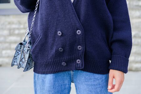 Close up of woman in dark blue oversize cardigan. Blue denim jeans. Street style Stock Photo