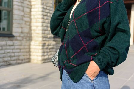 Close up of woman in green oversize cardigan. Blue denim jeans. Street style Stock Photo