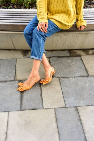 Close up of woman in yellow oversize sweater. Blue denim jeans, yellow sandals. Street style