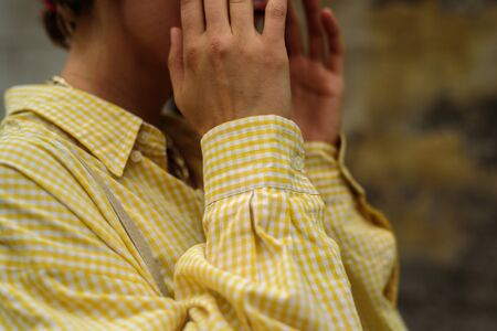 Close up of woman in male oversize yellow shirt. Street style Stock Photo