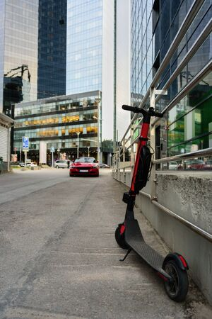 Electric kick scooter in modern city district with skyscrapers. Sharing kick scooter Stock Photo