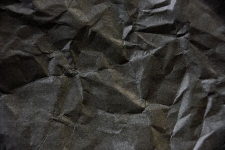 Crumpled black paper texture. Contrast abstract background