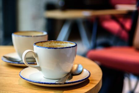 Two empty cups of coffee latte on cafe table. Chairs on background. Electric light Stock Photo