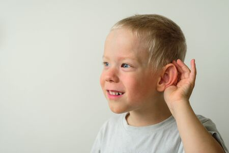 Little smiling boy with hearing gesture. Hearing children problems. Ear day Stock Photo