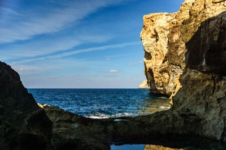 Azure Window remains cliff after collapse of arch. Deep Blue Hole on foreground. Coast of Island Gozo, Malta, Europe
