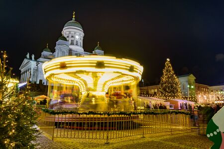 Christmas market on Senate Square in Helsinki, Finland. Cathedral, tree and spinning carousel at night Foto de archivo