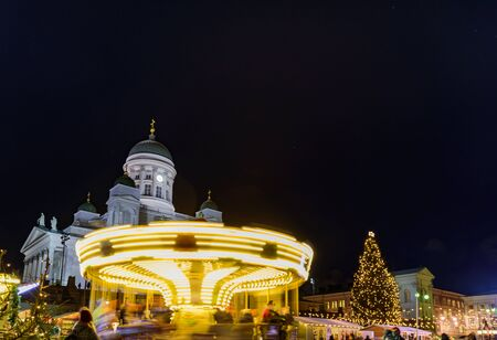 Christmas market on Senate Square in Helsinki, Finland. Cathedral, tree and spinning carousel at night