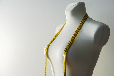 Tailor mannequin with yellow measuring tape on grey background