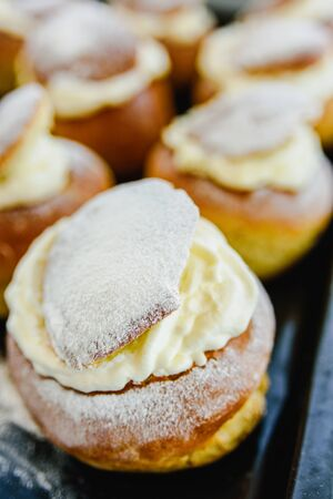 Semla swedish whipped cream filled bun on oven tray and grey concrete background. Shrove Tuesday dessert