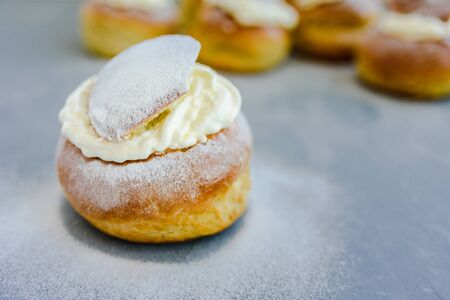 Semla swedish whipped cream filled bun on grey concrete background. Shrove Tuesday dessert Banco de Imagens