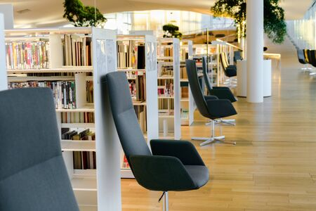 HELSINKI, FINLAND - December 28, 2019: Helsinki Central Library Oodi - modern library. Interior, reading space with a lot of books and chairs Redakční