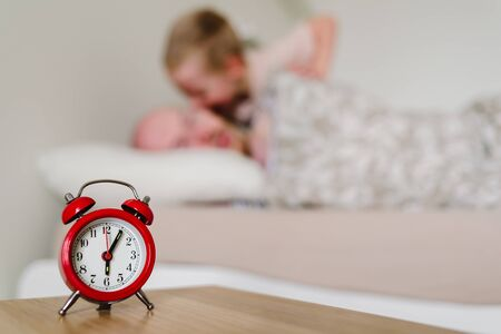 Red old style alarm clock with sleeping man on background. His child son waking him up. Parenthood and cosleeping concept