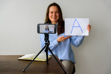 Woman teacher in shirt Recording video lesson at home for homeschooling children. Using smartphone